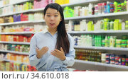Portrait of cheerful young Asian woman behind counter demonstrating hair dye products. Стоковое видео, видеограф Яков Филимонов / Фотобанк Лори
