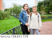 Mother and her middle school age daughter with backpack on back, student in grade 6 goes back to school at September. Стоковое фото, фотограф Кекяляйнен Андрей / Фотобанк Лори
