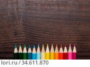 Multicolored pencils on the brown wooden table. Стоковое фото, фотограф Zoonar.com/Ruslan Ropat / age Fotostock / Фотобанк Лори