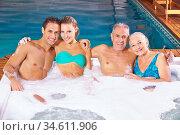 Zwei glückliche Paare baden im Whirlpool mit Schaum im Spa. Стоковое фото, фотограф Zoonar.com/Robert Kneschke / age Fotostock / Фотобанк Лори