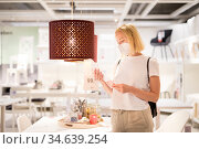 New normal during covid epidemic. Caucasian woman shopping at retail furniture and home accessories store wearing protective medical face mask to prevent spreading of corona virus. Стоковое фото, фотограф Matej Kastelic / Фотобанк Лори