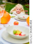 Lächelndes blondes Mädchen sitzt an einem gedeckten Tisch im Garten. Стоковое фото, фотограф Zoonar.com/Robert Kneschke / age Fotostock / Фотобанк Лори