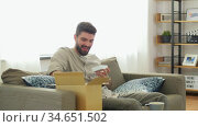 man opening parcel box with earphones at home. Стоковое видео, видеограф Syda Productions / Фотобанк Лори