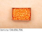 Rote Linsen in Karton auf braunem Hintergrund - Red lentils in carton... Стоковое фото, фотограф Zoonar.com/lantapix / easy Fotostock / Фотобанк Лори