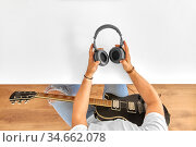 young man with headphones and guitar at table. Стоковое фото, фотограф Syda Productions / Фотобанк Лори