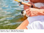 Hand eines Senioren mit der Angel im Sonnenschein beim Angeln am See. Стоковое фото, фотограф Zoonar.com/Robert Kneschke / age Fotostock / Фотобанк Лори