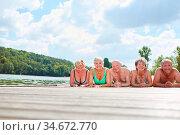 Gruppe Senioren als Rentner und Freunde liegen entspannt am Badesee... Стоковое фото, фотограф Zoonar.com/Robert Kneschke / age Fotostock / Фотобанк Лори