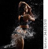 Fitness model posing in water splashes studio shot. Стоковое фото, фотограф Гурьянов Андрей / Фотобанк Лори