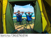 couple man and woman relaxing near camping tent on the sea. Стоковое фото, фотограф Константин Лабунский / Фотобанк Лори