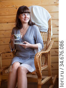 Smiling woman with a cup of coffee, portrait indoor, female sitting on a rattan chair. Стоковое фото, фотограф Кекяляйнен Андрей / Фотобанк Лори