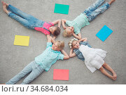 Four happy children laying on floor and smiling among colorful paper. Стоковое фото, фотограф Zoonar.com/Tatiana Badaeva / easy Fotostock / Фотобанк Лори