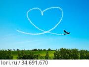 Flugzeug malt Herz am Himmel als Symbol für Liebe und Hochzeit. Стоковое фото, фотограф Zoonar.com/Robert Kneschke / age Fotostock / Фотобанк Лори