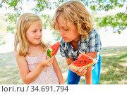 Kleines Mädchen gibt ihrem Bruder ein süßes Stück Melone im Sommer. Стоковое фото, фотограф Zoonar.com/Robert Kneschke / age Fotostock / Фотобанк Лори