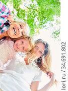 Glückliches Mädchen als Enkelin mit Mutter und Großmutter im Sonnenschein. Стоковое фото, фотограф Zoonar.com/Robert Kneschke / age Fotostock / Фотобанк Лори