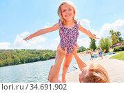 Vater hält seine Tochter in die Höhe und lässt sie fliegen im Sommerurlaub... Стоковое фото, фотограф Zoonar.com/Robert Kneschke / age Fotostock / Фотобанк Лори