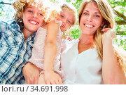 Glückliche Mutter mit zwei Geschwister Kindern im Sonnenschein in... Стоковое фото, фотограф Zoonar.com/Robert Kneschke / age Fotostock / Фотобанк Лори