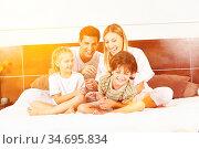 Lachende Familie sitzt mit zwei Kindern im Bett und kitzelt sich. Стоковое фото, фотограф Zoonar.com/Robert Kneschke / age Fotostock / Фотобанк Лори