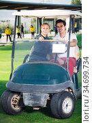 Young man and woman golfers riding golf cart. Стоковое фото, фотограф Яков Филимонов / Фотобанк Лори