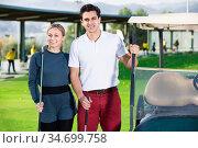 Male and female golf players driving golf cart at golf course. Стоковое фото, фотограф Яков Филимонов / Фотобанк Лори