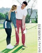 Golf trainer teaches a woman game. Стоковое фото, фотограф Яков Филимонов / Фотобанк Лори