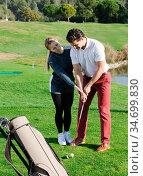 Golfer teaches a man the right to play golf. Стоковое фото, фотограф Яков Филимонов / Фотобанк Лори