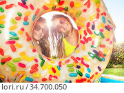 Two girls smile look out from inflatable doughnut. Стоковое фото, фотограф Сергей Новиков / Фотобанк Лори