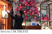 PARIS, FRANCE - DECEMBER 19, 2019: Consultant in the department of luxury bags on the background of the Christmas tree in the New Year's decorations in in Gallery Lafayette. Редакционное видео, видеограф Ирина Аринина / Фотобанк Лори