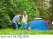 Junges Paar baut zusammen ein Zelt auf in der Natur im Camping Urlaub. Стоковое фото, фотограф Zoonar.com/Robert Kneschke / age Fotostock / Фотобанк Лори