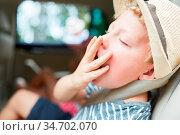 Junge hält die Hand vor den Mund beim Gähnen auf der Reise im Auto... Стоковое фото, фотограф Zoonar.com/Robert Kneschke / age Fotostock / Фотобанк Лори