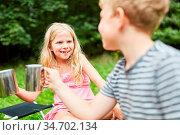 Mädchen und ihr Bruder auf dem Campingplatz trinken zusammen aus ... Стоковое фото, фотограф Zoonar.com/Robert Kneschke / age Fotostock / Фотобанк Лори