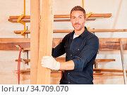 Junger Handwerker als Schreiner Lehrling trägt Balken aus Holz in... Стоковое фото, фотограф Zoonar.com/Robert Kneschke / age Fotostock / Фотобанк Лори