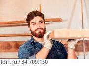 Junger Arbeiter oder Schreiner trägt einen Balken in der Schreinerei... Стоковое фото, фотограф Zoonar.com/Robert Kneschke / age Fotostock / Фотобанк Лори
