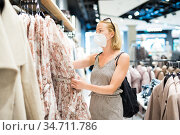Fashionable woman wearing protective face mask shopping clothes in reopen retail shopping store. New normal lifestyle during corona virus pandemic. Стоковое фото, фотограф Matej Kastelic / Фотобанк Лори