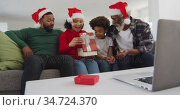 Multi-generation family opening gift box while having video chat on his laptop. Стоковое видео, агентство Wavebreak Media / Фотобанк Лори