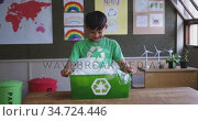Boy holding a recycle container in the class at school. Стоковое видео, агентство Wavebreak Media / Фотобанк Лори