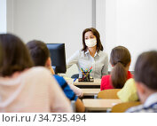 teacher wearing face protective mask at school. Стоковое фото, фотограф Syda Productions / Фотобанк Лори