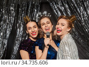 women with microphone singing at christmas party. Стоковое фото, фотограф Syda Productions / Фотобанк Лори