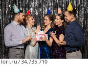 happy friends in party hats with birthday gift. Стоковое фото, фотограф Syda Productions / Фотобанк Лори