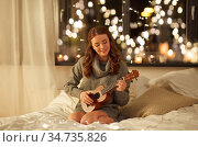 happy young woman playing guitar in bed at home. Стоковое фото, фотограф Syda Productions / Фотобанк Лори