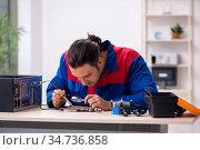 Young male repairman repairing computer. Стоковое фото, фотограф Elnur / Фотобанк Лори