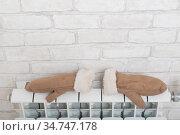 Women's mittens dry on the radiator in winter. Стоковое фото, фотограф Михаил Решетников / Фотобанк Лори