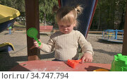 Little blond girl playing with rake and sieve on table at playground. Стоковое видео, видеограф Сергей Старуш / Фотобанк Лори