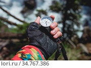 A gloved hand holds a magnetic compass against the background of a... Стоковое фото, фотограф Zoonar.com/Ian Iankovskii / easy Fotostock / Фотобанк Лори