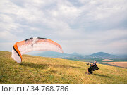 The paraglider opens his parachute before taking off from the mountain... Стоковое фото, фотограф Zoonar.com/Ian Iankovskii / easy Fotostock / Фотобанк Лори