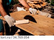 Hard working woodworker cutting wooden plank, focus on saw. Стоковое фото, фотограф Zoonar.com/Oksana Shufrych / easy Fotostock / Фотобанк Лори