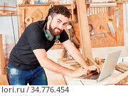 Junger Handwerker in der Werkstatt schreibt eine Email auf dem Laptop... Стоковое фото, фотограф Zoonar.com/Robert Kneschke / age Fotostock / Фотобанк Лори