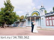 A beautiful couple of newlyweds are hugging against the background... Стоковое фото, фотограф Zoonar.com/Ian Iankovskii / easy Fotostock / Фотобанк Лори
