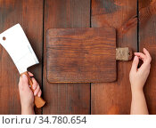 Very old empty wooden rectangular cutting board and hands hold a large... Стоковое фото, фотограф Zoonar.com/Danko Natalya / easy Fotostock / Фотобанк Лори