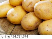 Raw fresh young potatoes at wooden table in home kitchen. Стоковое фото, фотограф Яков Филимонов / Фотобанк Лори