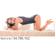 Sexy brunette wearing black body in bed staying on her knees view. Стоковое фото, фотограф Zoonar.com/Andrey Guryanov / easy Fotostock / Фотобанк Лори